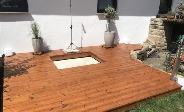 Eine Holzterrasse mit integrierter Gartendusche entsteht